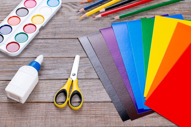 Folhas de papel, cola e tesoura em uma mesa de madeira. projeto de arte infantil, um artesanato para crianças. artesanato para crianças.