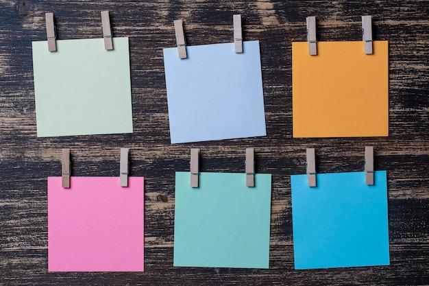 Folhas de papel colorido vazio para anotações com prendedores de roupa em fundo de madeira. cartões em branco no modelo de maquete. prendedores de roupa de madeira com folhas de papel. conceito de negócio, copie o espaço