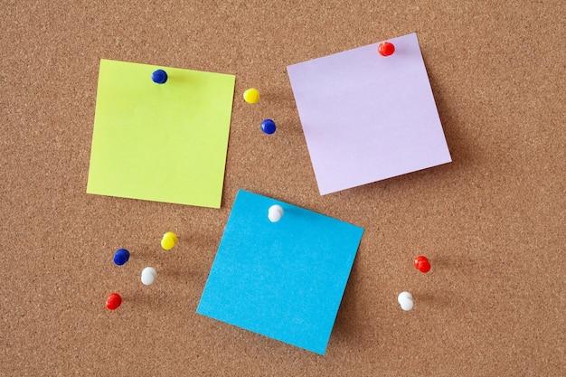 Folhas de papel de anotações amarelas, roxas e azuis presas a um quadro de cortiça entre vários botões. conceito de negócios.