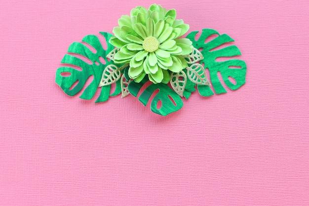 Folhas de papel e flor de papel artesanal verde sobre um fundo textural papel rosa