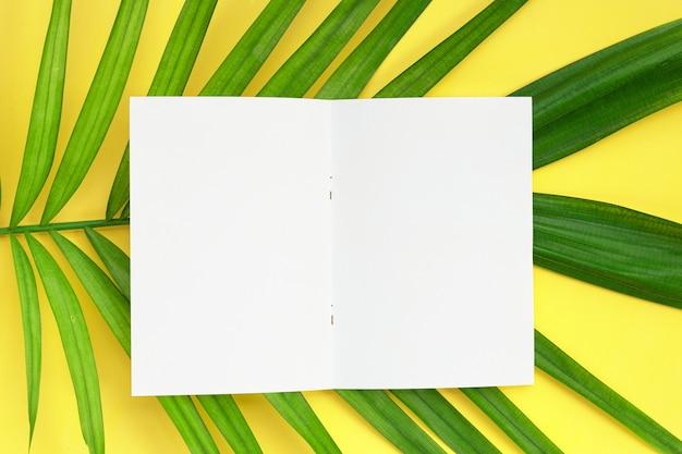 Folhas de papel em branco com palmeiras tropicais em fundo amarelo. copie o espaço