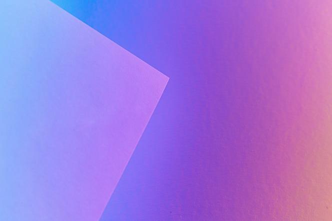 Folhas de papel em branco enroladas em uma iluminação de néon roxo