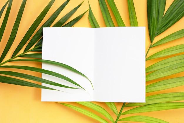 Folhas de papel em branco na palmeira tropical sobre fundo amarelo.