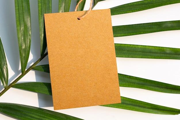 Folhas de papel pardo em branco sobre palmeiras tropicais. copie o espaço
