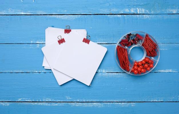 Folhas de papel quadradas em branco e artigos de papelaria com clipes de papel e clipes em fundo azul de madeira
