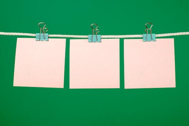Folhas de papel rosa em branco pendurado na corda