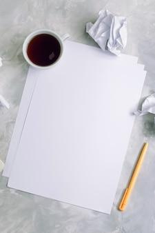 Folhas de papel vazio e papel amassado sobre fundo de concreto: vista de cima, copie o espaço