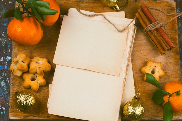 Folhas de papel velho vazio, canela, bolas de natal douradas e mesa de madeira vista superior de tangerinas