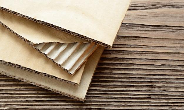 Folhas de papelão ondulado em fundo de madeira áspero. folha rasgada.