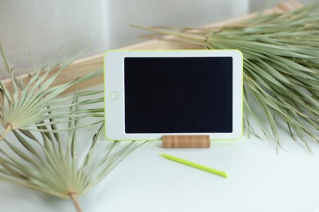 Folhas de pastilha branca com caneta na mesa branca com palmeiras secas ao redor. escritório em casa enquanto auto-isolamento, trabalhando em casa. educação on-line, e-learning em quarentena.