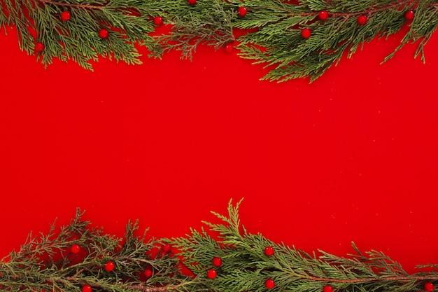 Folhas de pinheiro de natal em um fundo de moldura vermelha com copyspace