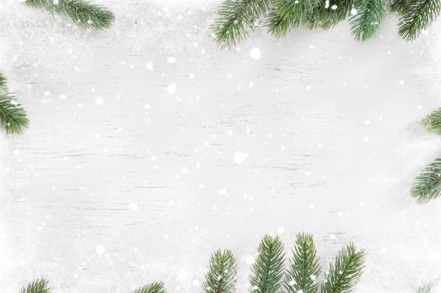 Folhas de pinheiro decoradas como uma moldura em um fundo branco de madeira