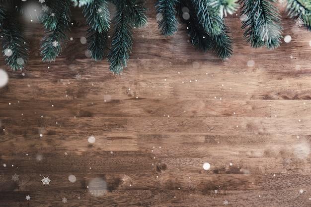 Folhas de pinheiro verde árvore de natal e neve no fundo da mesa de madeira