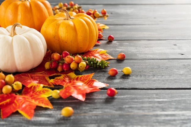 Folhas de plátano e abóbora do outono no fundo de madeira velho. conceito de dia de ação de graças.