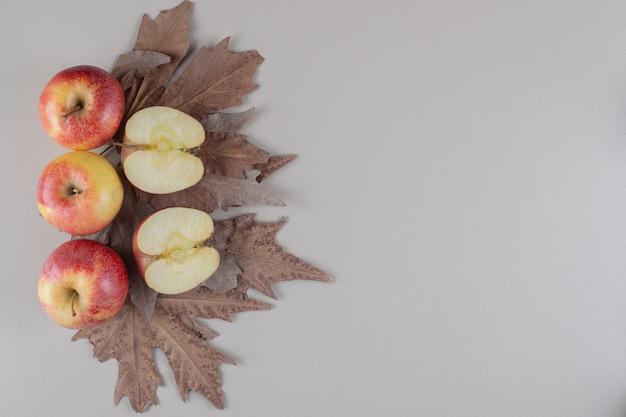 Folhas de plátano sob um feixe de maçãs fatiadas e inteiras em mármore