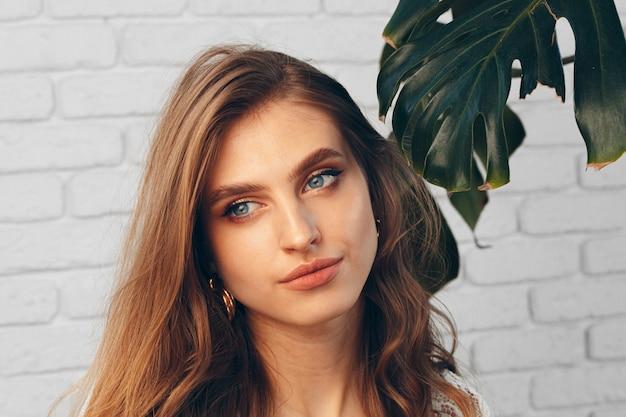 Folhas de retrato de uma linda mulher com monstera. foto criativa