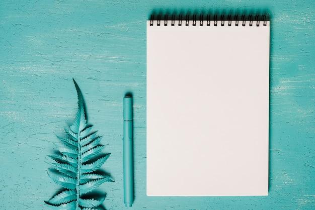 Folhas de samambaia; caneta e bloco de notas espiral em branco no fundo texturizado turquesa