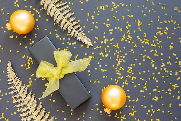 Folhas de samambaia douradas brilhantes e caixa de presente com bolas de natal em um fundo preto com estrelas douradas brilhantes
