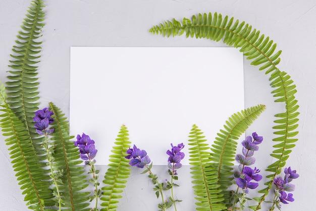 Folhas de samambaia verde com flores e papel na mesa