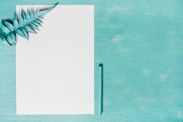 Folhas de samambaia verde no papel e caneta contra fundo turquesa