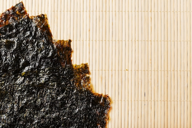 Folhas de sushi nori na superfície do bambu