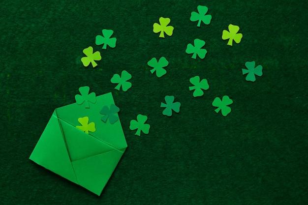 Folhas de trevo cortadas em papel colorido. papel de parede para o dia de são patrício. o trevo é um símbolo de boa sorte.
