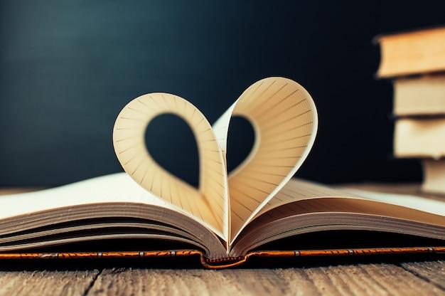 Folhas de um caderno em uma gaiola envolto em forma de coração.