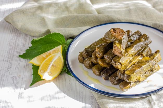 Folhas de uva recheadas com arroz e especiarias, servidas com azeite e limão fresco