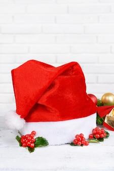 Folhas de visco com chapéu de natal na mesa no fundo da parede de tijolos