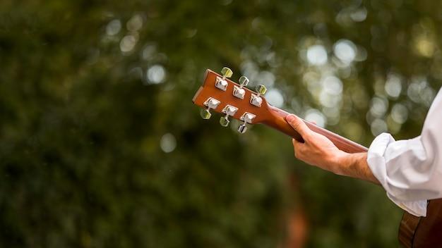 Folhas desfocadas e homem tocando guitarra por trás da foto