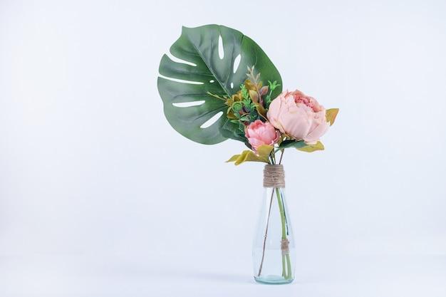 Folhas e flores artificiais em frasco de vidro branco.