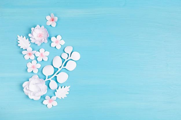 Folhas e flores tropicais de papel sobre a parede rosa pastel. férias exóticas de verão, vista superior plana