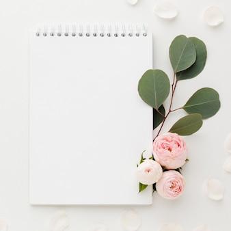Folhas e rosas com bloco de notas