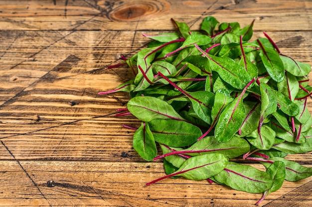 Folhas frescas de acelga crua, mangold, acelga suíça na mesa de madeira