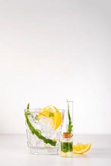 Folhas frescas de aloe vera e suco de aloe vera em vidro no fundo branco
