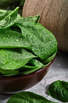 Folhas frescas de espinafre com gotas de orvalho em um prato de argila sobre um fundo cinza. copie o espaço, alimentos frescos do jardim.