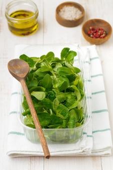 Folhas frescas de salada crua em caixa de plástico na mesa de madeira clara. foco seletivo. vista do topo. copie o espaço.