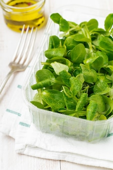 Folhas frescas de salada crua em caixa de plástico na mesa de madeira clara. foco seletivo.