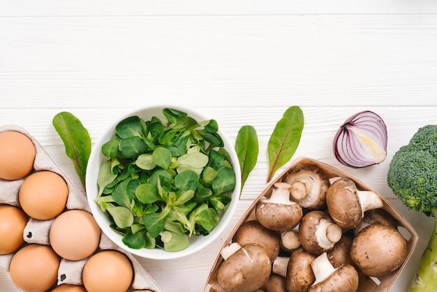 Folhas frescas de salada de milho; ovos; cebola; brócolis e cogumelo na mesa branca