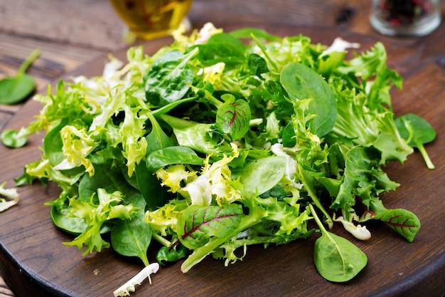 Folhas frescas de salada mista sobre um fundo de madeira.
