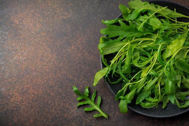 Folhas frescas e cruas de salada de rúcula no prato de cerâmica preta sobre fundo escuro de concreto ou pedra.