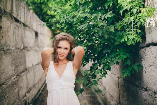 Folhas linda garota feliz com cabelo natural encaracolado em vestido branco perto de árvore verde.
