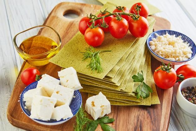 Folhas para fazer lasanha com espinafre e ingredientes: tomate cereja, queijo, manteiga, pimentão e ervas.