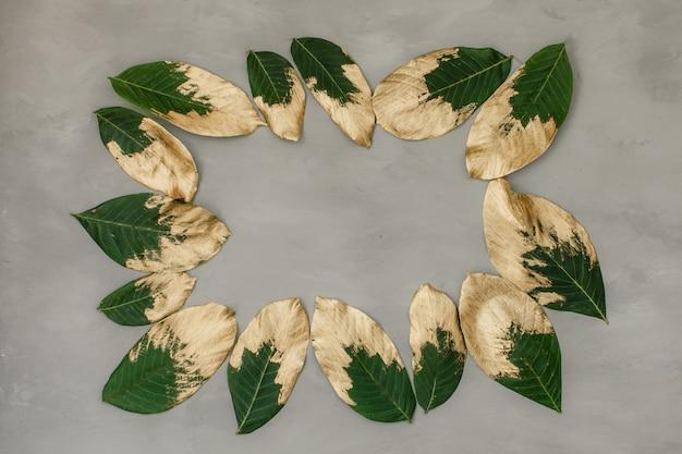 Folhas pintadas de ouro e verdes no quadro