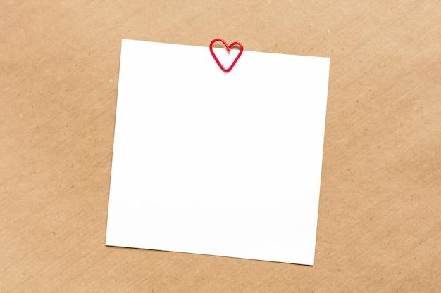 Folhas quadradas vazias brancas sobre fundo de papel kraft clipe de papel vermelho em forma de coração