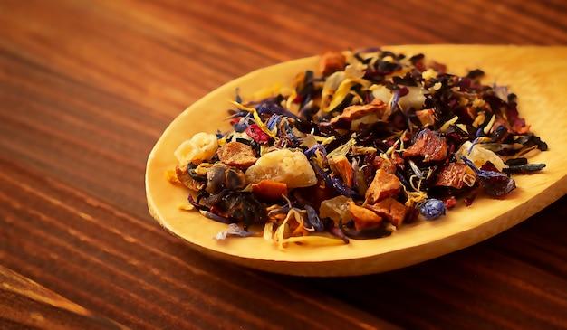 Folhas secas de chá em uma colher de pau em uma mesa de madeira