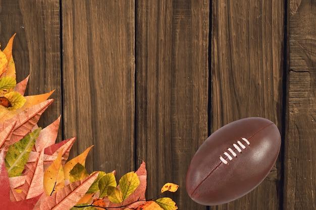 Folhas secas e bola de rugby em um assoalho de madeira