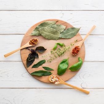 Folhas secas e especiarias na bandeja de madeira redonda