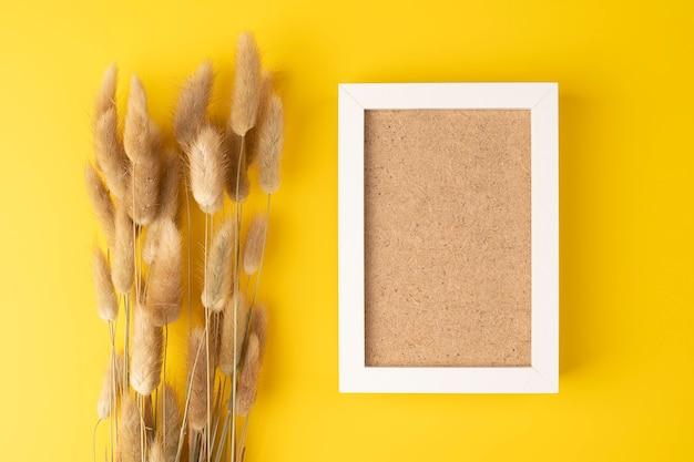 Folhas secas e fofas de rabo de coelho flores lagurus de grama em fundo amarelo com foto framepom pom plant
