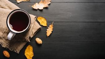 Folhas secas e miolo perto de bebida e tecido